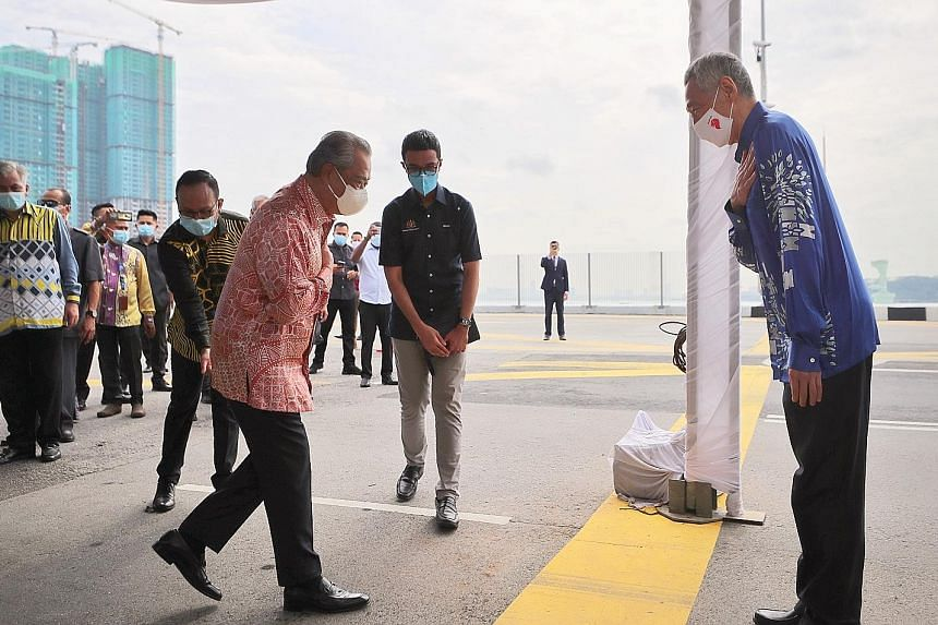 PM Lee and Tan Sri Muhyiddin greeting each other yesterday at the Causeway, where the two leaders witnessed the ceremony to mark the resumption of the Johor Baru-Singapore Rapid Transit System Link. The thick yellow line marks the international bound