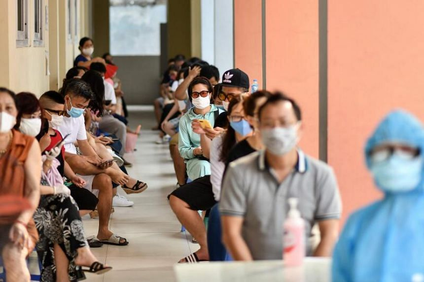 Residents wait to be tested at a makeshift rapid testing centre in Hanoi, on July 31, 2020.