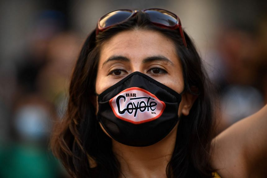 A woman wearing a face mask with a bar logo takes part in a Barcelona protest against the closure of nightclubs and event halls after a surge in coronavirus cases.