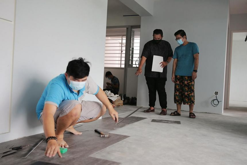 Renodiction's founder Azri Abbas (second from right) with his client Abdul Hadi (right) at Mr Hadi's Sengkang flat.