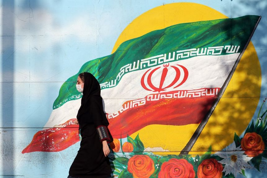 An Iranian woman wearing a face mask walks past a mural of Iran's national flag in Teheran.
