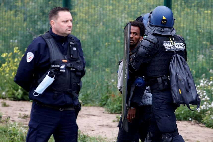 French police officers detain a migrant during the dismantling of a makeshift camp in Calais, on July 10, 2020.