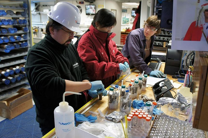 Researchers (from left) Yuki Morono, Xiao-Hua Zhang and Lisa Crowder preparing core samples taken from the bottom of the South Pacific Gyre for analysis.