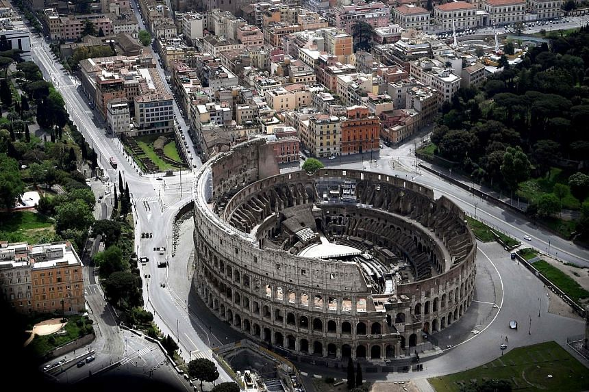 An empty Colosseum in Rome, as well as the deserted streets around it, during the lockdown in Italy earlier this year aimed at curbing the spread of the coronavirus. A new report shows that such lockdowns led to a drop of up to 50 per cent in the glo