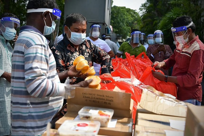 Safety coordinator and supervisor Billal Hossein (second from left) sorting out meals prepared for foreign workers at a factory in Sungei Kadut yesterday. About 6,000 migrant workers staying in 78 factory-converted dormitories enjoyed free meals from