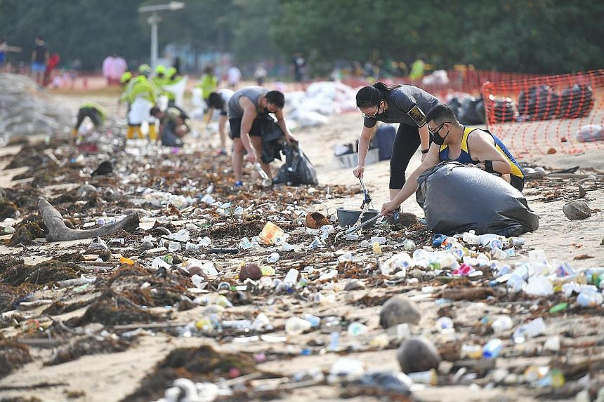 Volunteers cleaning up the beach at East Coast Park yesterday. The trash included plastic snack wrappers, glass bottles and slippers. One beachgoer said the debris also included wood fragments with sharp nails sticking out, which posed a danger to th