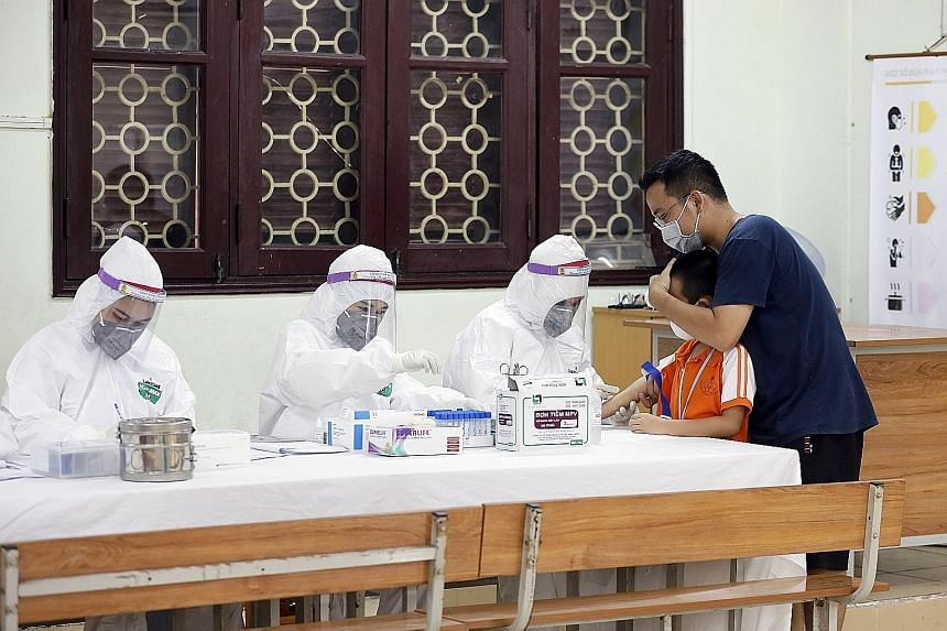 A boy who recently returned from Danang getting his blood tested at a makeshift rapid testing centre for Covid-19 in Hanoi yesterday. PHOTO: EPA-EFE