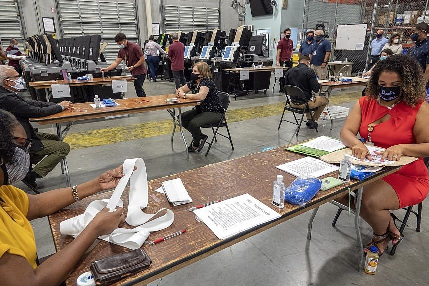 Employees conducting logic and accuracy testing of the voting equipment at the Miami Dade-County Election Department's office in Florida on Wednesday. The state will hold its primary election on Aug 18. President Donald Trump has claimed, without evi