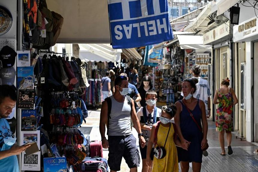 Tourists wearing face masks walk in Athens' main commercial district on July 29, 2020.