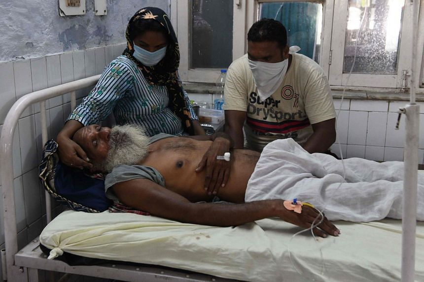 Relatives sit with patient Sawinder Singh after he allgedly drank spurious alcohol on Aug 1, 2020.