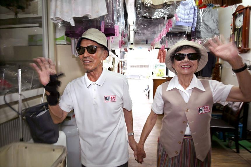 Mr Chang Wan-ji (left) and his wife Hsu Sho-er pose at their laundry store in Taichung, Taiwan, on July 30, 2020.