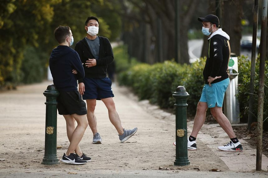 People wear face masks along the Tan walking track in Melbourne on July 24, 2020.