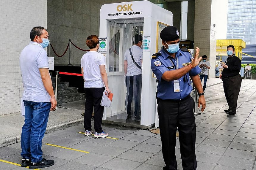 People wearing masks and maintaining social distancing while waiting in line to enter a disinfection chamber at Plaza OSK in Kuala Lumpur. PHOTO: BLOOMBERG