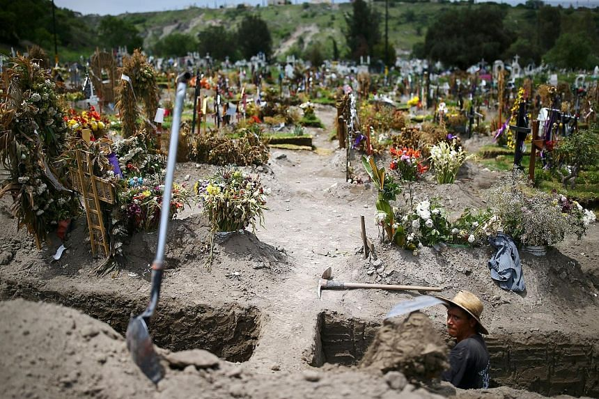 A cemetery worker digging new graves at the Xico cemetery on the outskirts of Mexico City on Friday, as Mexico overtook Britain to become the country with the third-most deaths due to Covid-19.