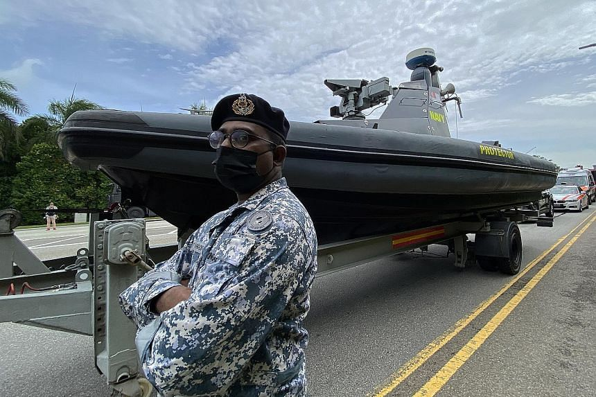 ME2 Vaengadis Waran, 40, and the Republic of Singapore Navy's Protector Unmanned Surface Vessel, one of the assets in the mobile column. Vehicles lined up in preparation for the mobile column rehearsal yesterday. The column will travel on five routes