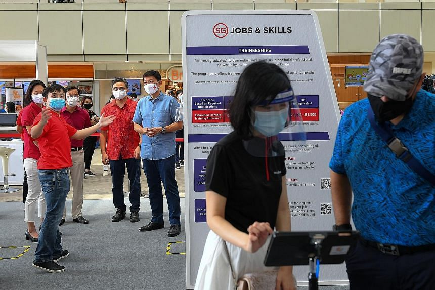 Senior Minister of State for Foreign Affairs and Transport Chee Hong Tat (in light blue top) being briefed by Mr Toh Swee Chien (in red polo T-shirt) of SkillsFuture Singapore at a job fair at HDB Hub in Toa Payoh yesterday, along with (from left) MP