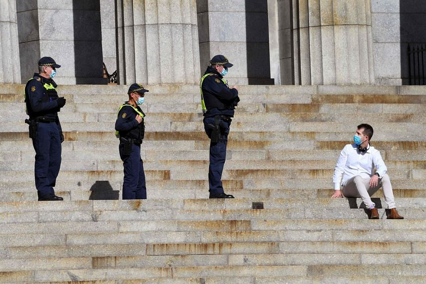 Protective Services officers speak to a man on the steps of the Shrine of Remembrance in Melbourne, on July 31, 2020.