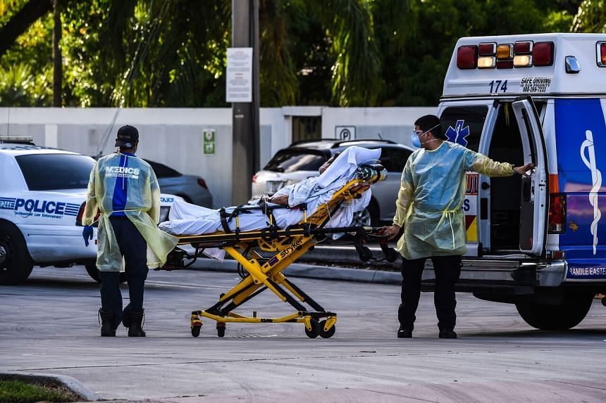 Medics transfer a patient from an ambulance outside a hospital where Covid-19 patients are treated in Florida on July 30, 2020.