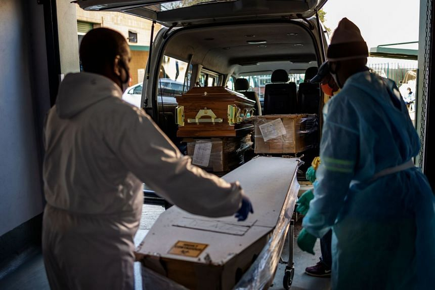 Undertakers in Soweto load a coffin containing the remains of a Covid-19 patient into a van  on July 24, 2020.