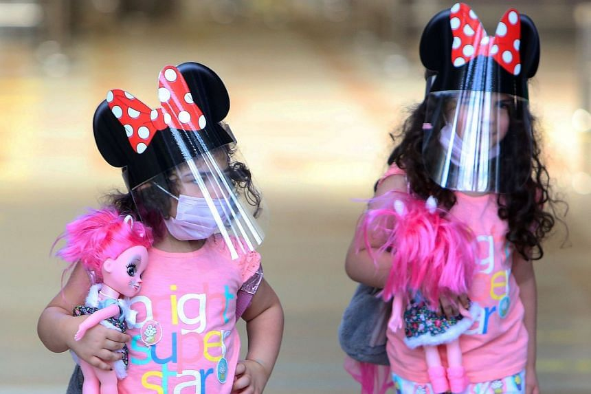 Children travelling from Kuwait City's international airport wear face masks and shields as protections against coronavirus on Aug 1, 2020.