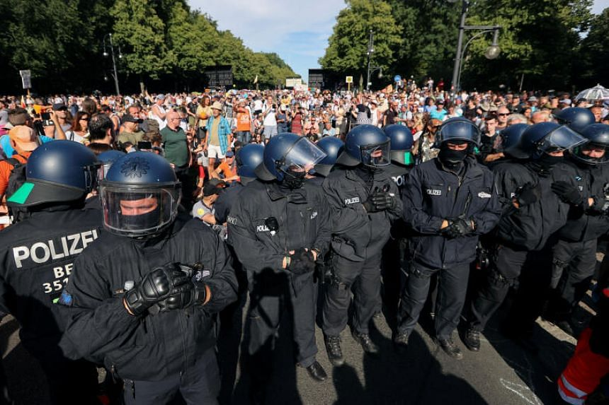 Police officers stand next to protesters near the Brandenburg Gate in Berlin, on Aug 1, 2020.