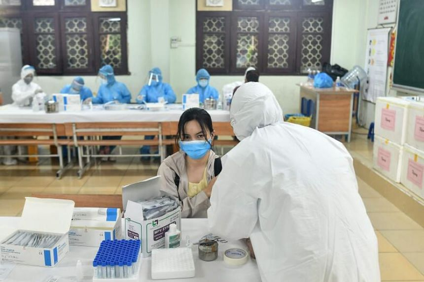 A health worker collects a blood sample from a resident at a makeshift rapid testing centre in Hanoi on Aug 1.
