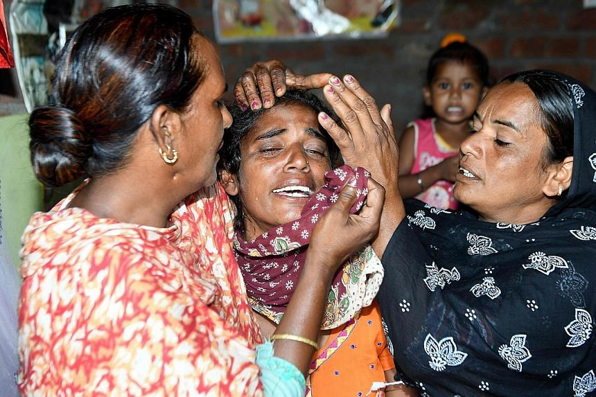 Punjab resident Amandeep Kaur (centre) being consoled by relatives yesterday after her husband Kuldeep Singh died from drinking illegal alcohol.