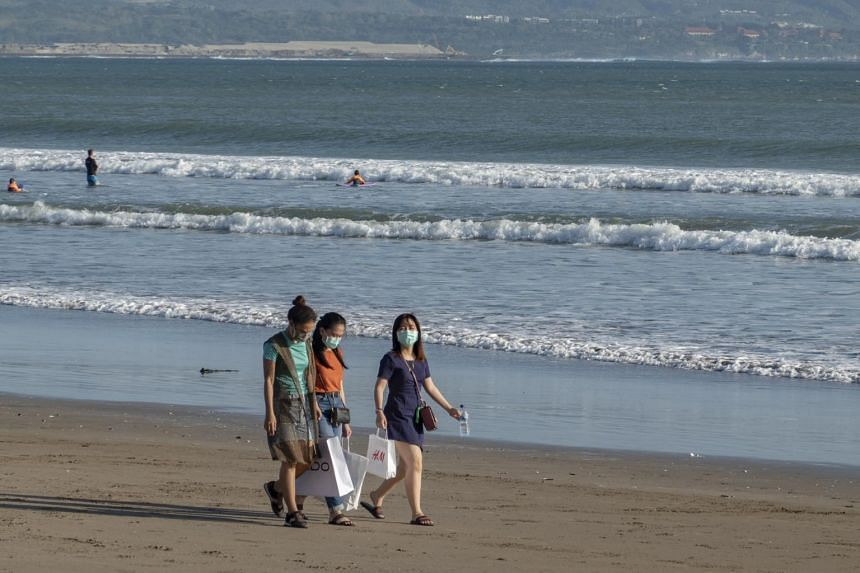 Tourists wear face masks as they walk at a beach in Seminyak, Bali, Indonesia, on July 31, 2020.