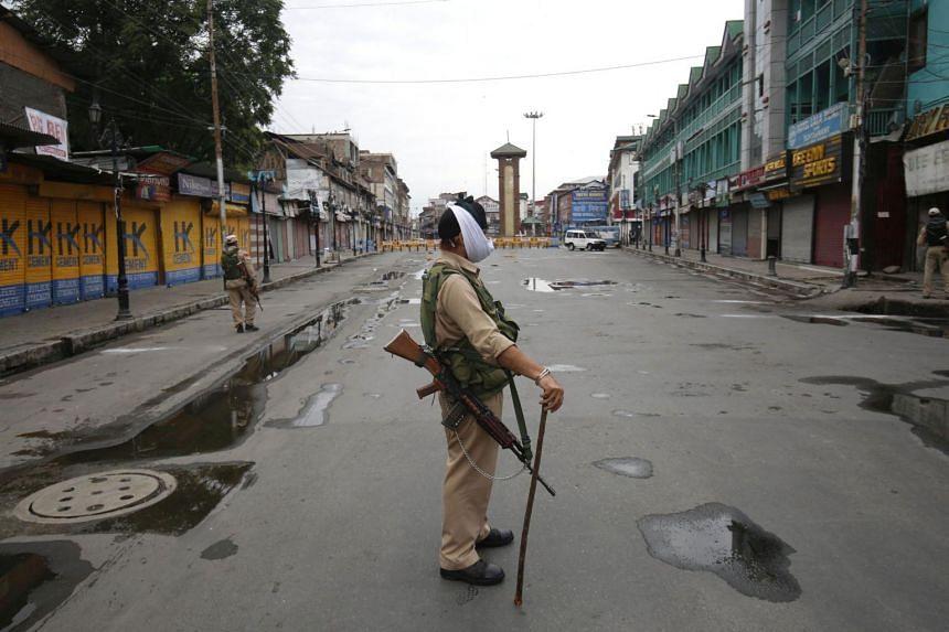 Police patrol near a closed market in Srinagar, India, on Aug 1, 2020.