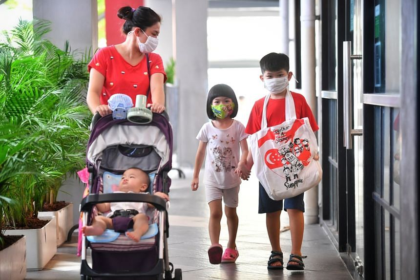 Siblings Thana (centre) and Kaden Chen, with baby brother Ryan and their mother, Madam Lin Kolee, collecting the Singapore Together pack from Tampines West Community Club, on July 20, 2020.