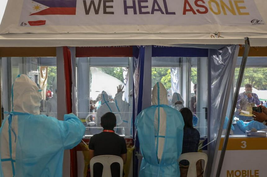 Health workers perform swab tests to government workers in Quezon City, northeast of Manila, on July 30, 2020.