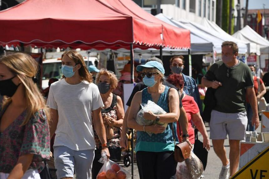 People wearing face coverings shop at the Santa Monica Farmers' Market, on Aug 1, 2020.