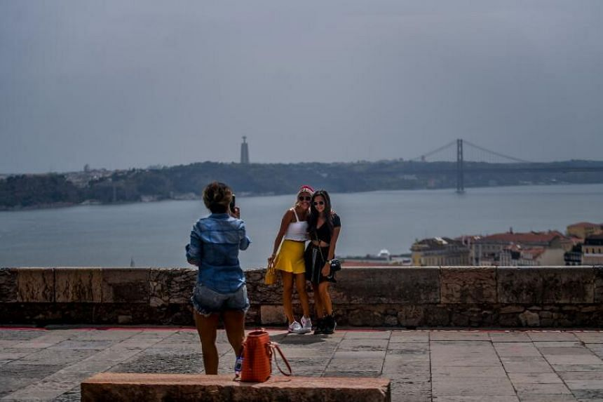 Tourists take pictures at Sao Jorge castle viewpoint in Lisbon on July 20, 2020.