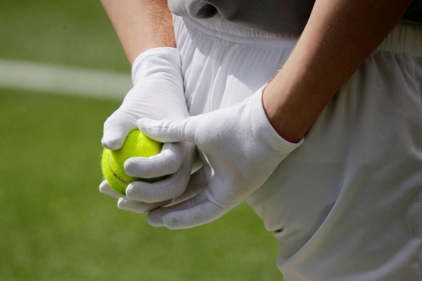 A person wearing protective gloves holds a tennis ball during an exhibition match in Germany.