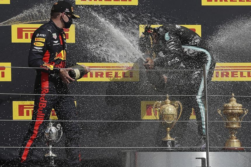 Race winner Lewis Hamilton (above) inspecting the punctured tyre on his Mercedes before celebrating on the British Grand Prix podium with runner-up Max Verstappen.