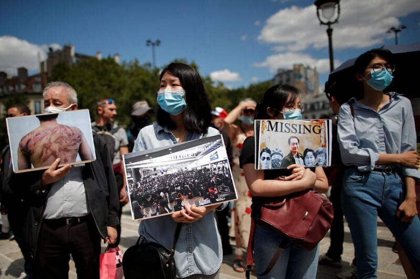 People wearing masks hold pictures as they demonstrate in support of Hong Kong protesters in Paris, on July 11, 2020.