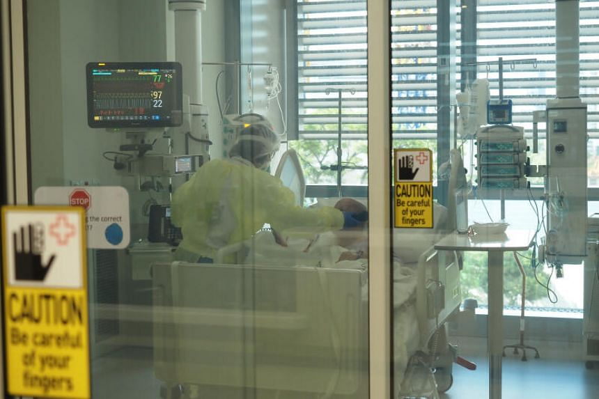 A photo taken on July 21, 2020, showing a medical worker tending to a patient inside an ICU at the National Centre for Infectious Diseases.