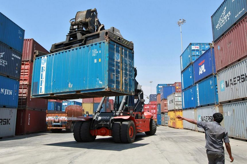 In a photo taken on March 16, 2012, a mobile crane prepares to stack a container at a port in the southern Indian city of Chennai.