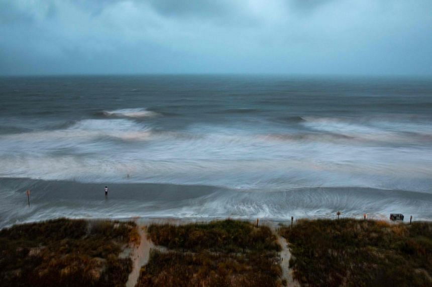 Large surf is swirled by the wind while a person stands on the shore as Hurricane Isaias approaches North Myrtle Beach, South Carolina, on Aug 3, 2020.