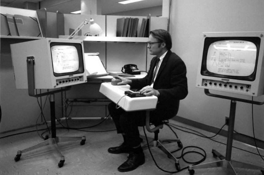 An undated photo provided via SRI International of William English testing the first computer mouse, a device envisioned by his colleague Douglas Engelbart, that was unveiled in 1968.