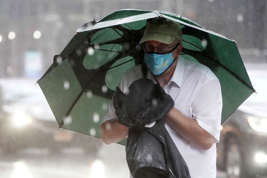 A man with an umbrella crosses a street as New York City starts to feel the effects of Tropical Storm Isaias, Aug 4, 2020.