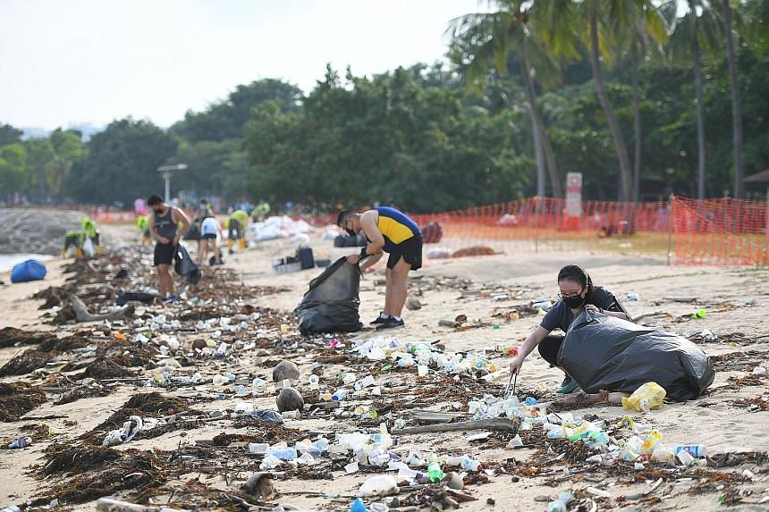 Volunteers picking up trash at East Coast Park last Friday. The National Environment Agency says there has been an almost 90 per cent increase in the amount of flotsam collected from East Coast Park beaches during the south-west monsoon season, compa