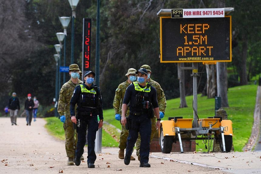 Police officers and soldiers patrol a popular running track in Melbourne on Aug 4, 2020.
