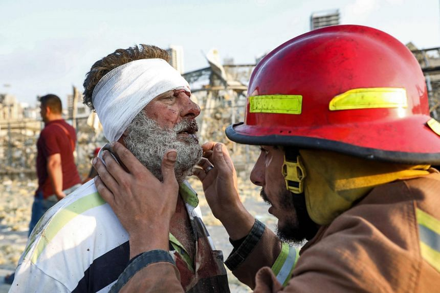 A wounded man is checked by a fireman near the scene.