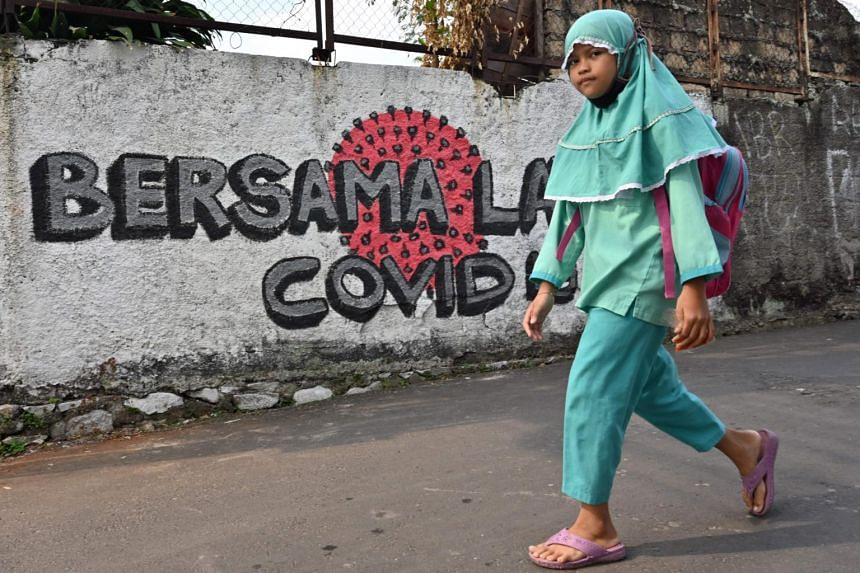 """A girl walks past a mural reading """"together against Covid-19"""" in Jakarta on Aug 4, 2020."""