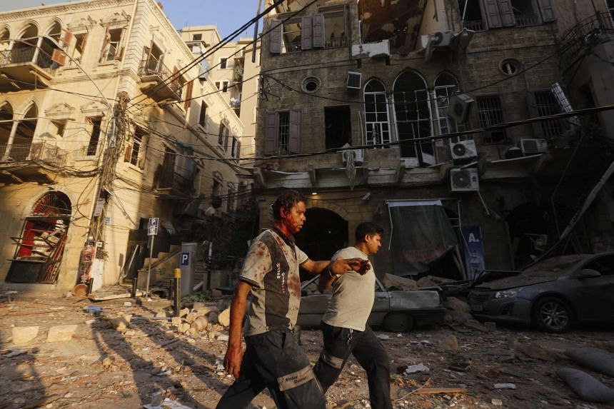 A wounded man is helped as he walks through debris in Beirut's Gemmayzeh district following the incident.
