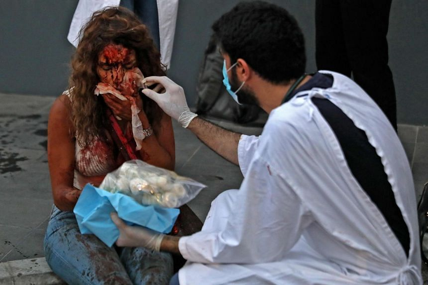 A wounded woman receives help outside a hospital following the explosion.
