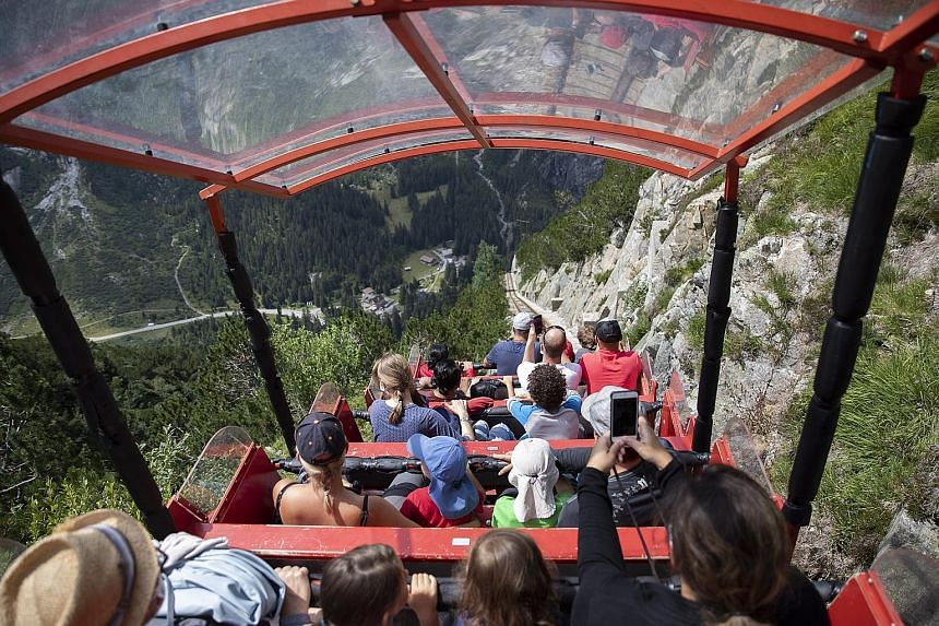 """Above: Tourists taking a ride on the Gelmerbahn funicular in Bern, Switzerland. The country's public health authorities say the effectiveness of its Covid-19 tracker app is difficult to measure because of its """"privacy by design"""". Meanwhile, Ireland's"""