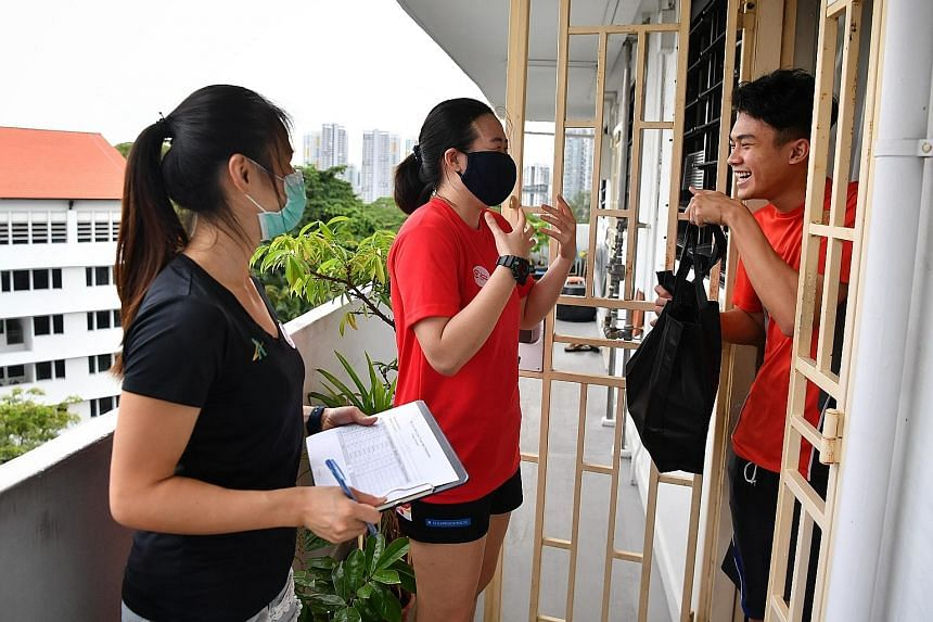 National rugby players Amanda Ng (centre) and Loo Zi Jia distributing frozen meals to York Hill resident Lim Muhammad Hakim during the Do Good, Send Love campaign for people in Central Singapore District yesterday. The tie-up between Elpis @ Hideout,