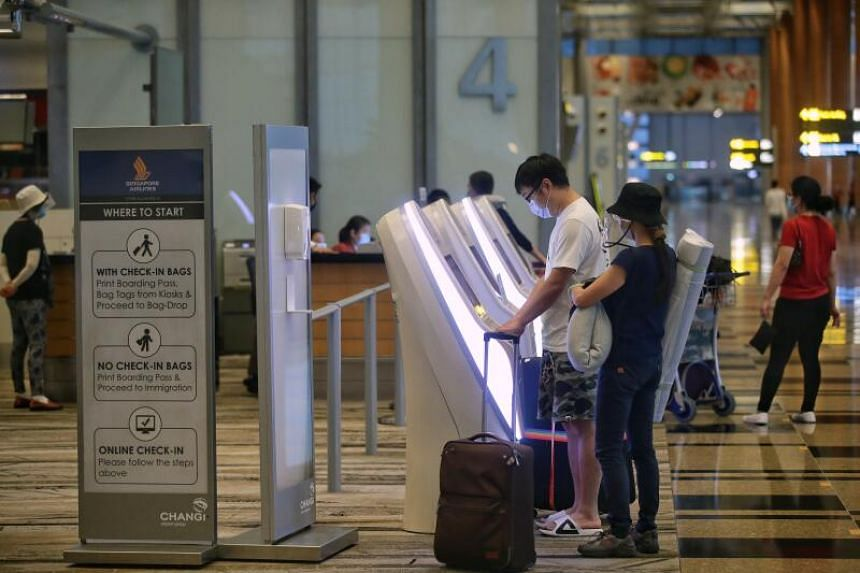 Travellers checking in at Changi Airport Terminal 3 departure hall on June 8, 2020.